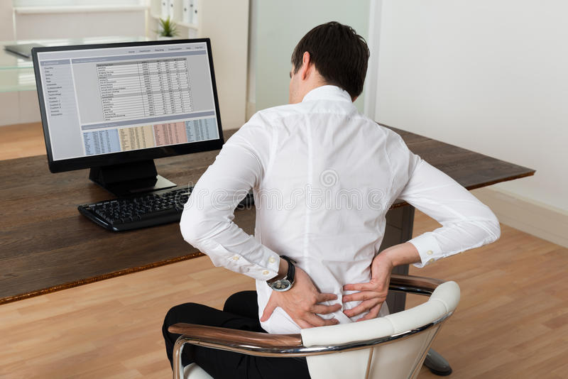 Geschäftsmann, der unter Rückenschmerzen am Schreibtisch leidet lizenzfreie stockbilder