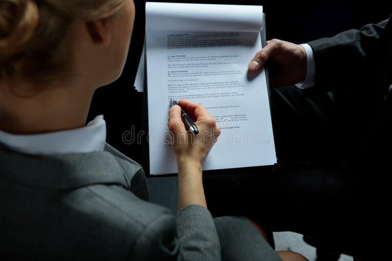 Geschäftsmann, der unterzeichnenden Vertrag des Klemmbrettes und der Geschäftsfrau hält lizenzfreies stockbild