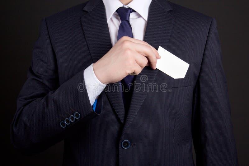 Geschäftsmann, der Visitenkarte aus seiner Klagentasche heraus hält lizenzfreie stockbilder