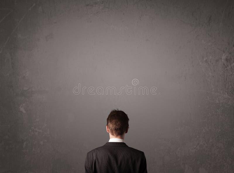 Geschäftsmann, der vor einer leeren Wand steht lizenzfreie stockbilder