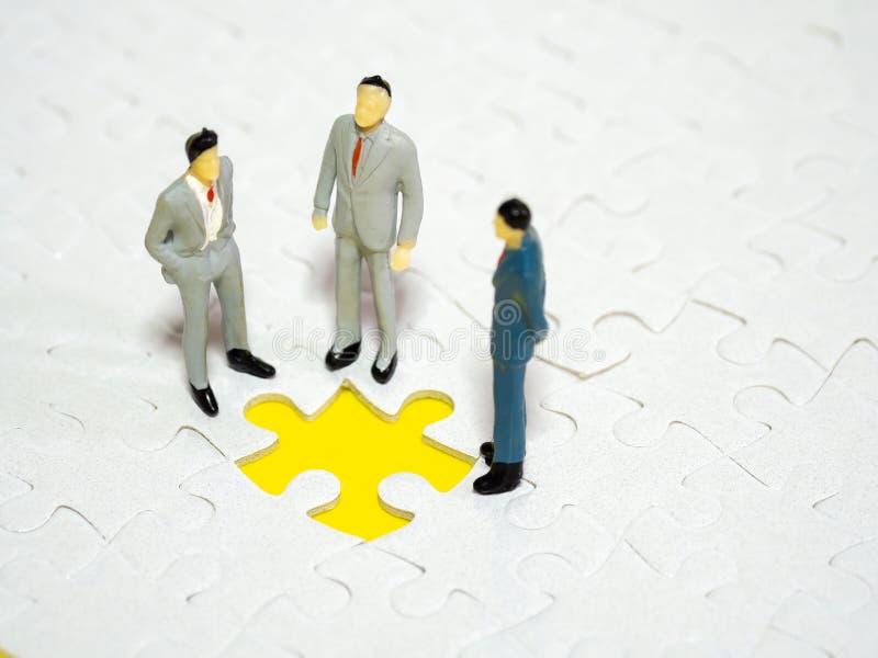 Geschäftsmann, der vor fehlender Stücklaubsäge auf dem gelben Hintergrund steht stockbild