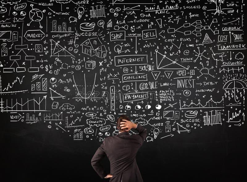 Geschäftsmann, der vor gezogenen Diagrammen auf einer Tafel steht lizenzfreies stockbild