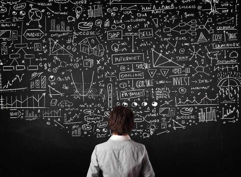 Geschäftsmann, der vor gezogenen Diagrammen auf einer Tafel steht stockbild