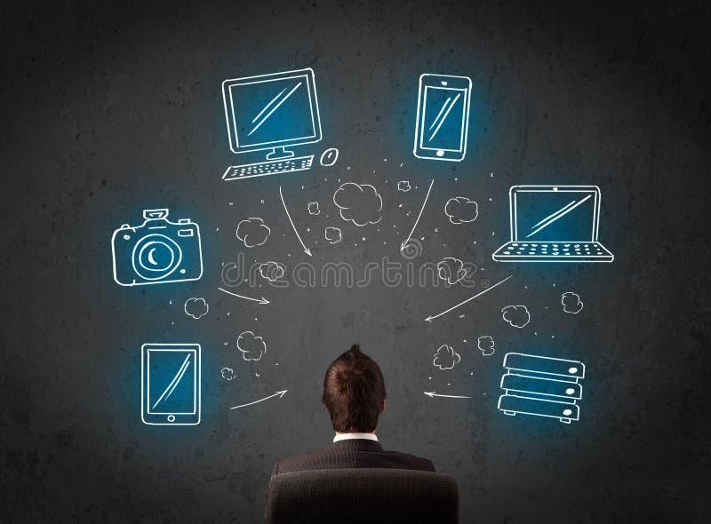 Geschäftsmann, der vor gezogenen Multimediaikonen sitzt lizenzfreies stockfoto