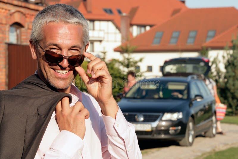 Geschäftsmann, der vor Haus steht lizenzfreie stockfotos