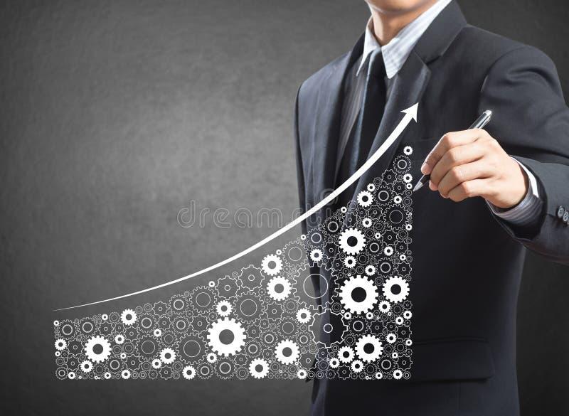 Geschäftsmann, der wachsende Wirtschaft und die Industrie dargestellt durch Gänge zeichnet stockfotografie