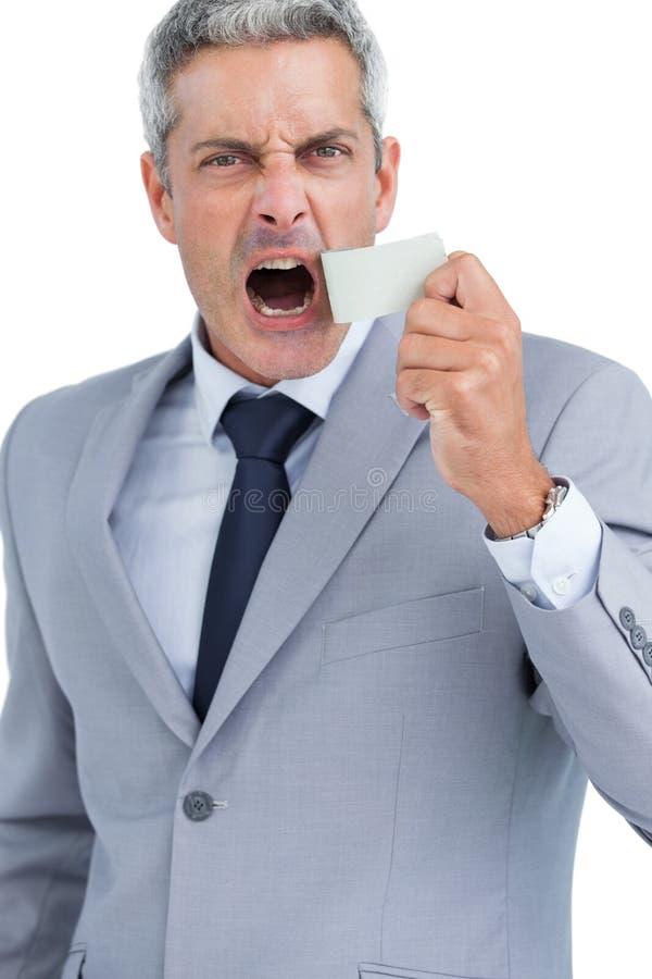 Geschäftsmann, der weg vom Panzerklebeband vom Mund zerreißt lizenzfreies stockfoto