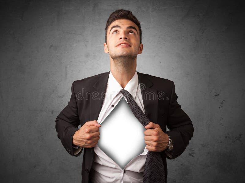 Geschäftsmann, der weg von seinem Hemd mit weißem copyspace auf Kasten zerreißt lizenzfreie stockfotografie