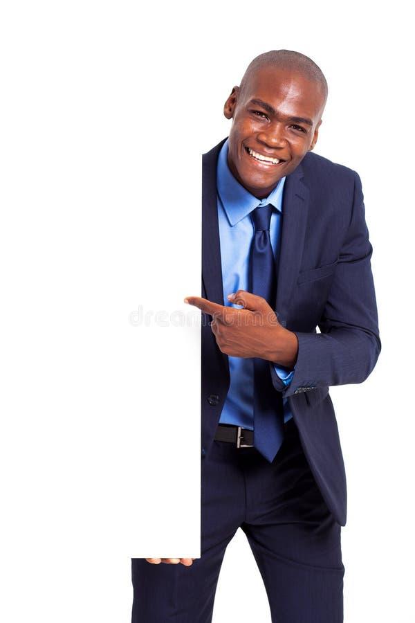Geschäftsmann, der weißen Vorstand zeigt lizenzfreies stockfoto