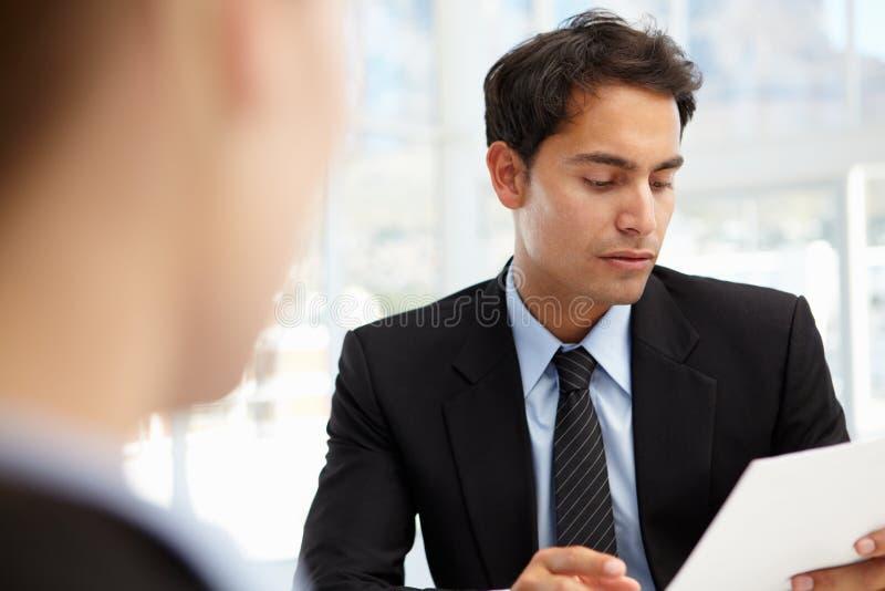 Geschäftsmann, der weiblichen Angestellten interviewt lizenzfreies stockbild