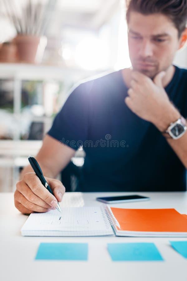 Geschäftsmann, der wichtige Anmerkungen im Bürotagebuch notiert lizenzfreie stockfotografie