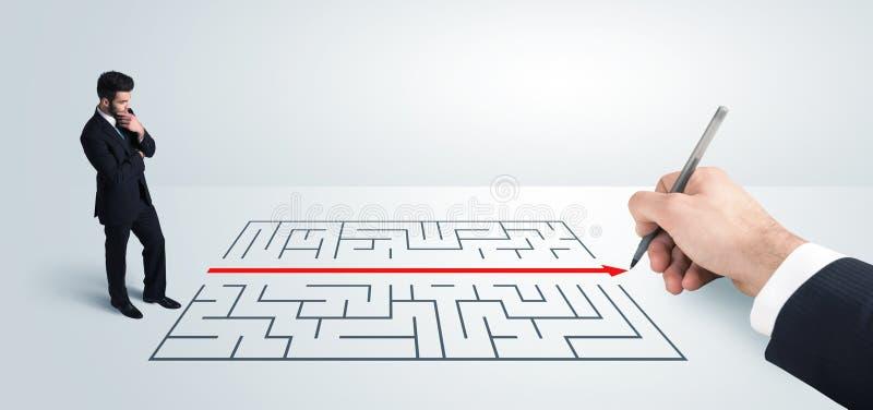 Geschäftsmann, der Zeichnungslösung zur Hand nach Labyrinth sucht lizenzfreie stockfotografie