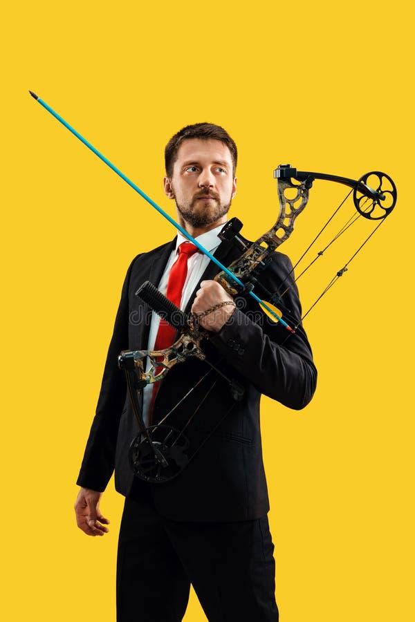 Geschäftsmann, der Ziel mit dem Pfeil und Bogen, lokalisiert auf gelbem Hintergrund anstrebt lizenzfreies stockfoto