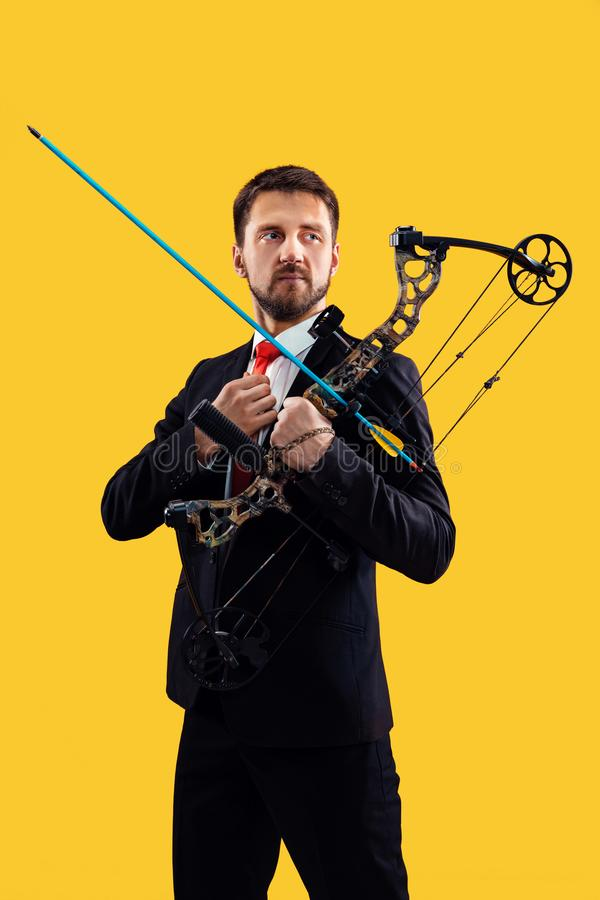 Geschäftsmann, der Ziel mit dem Pfeil und Bogen, lokalisiert auf gelbem Hintergrund anstrebt lizenzfreie stockfotos