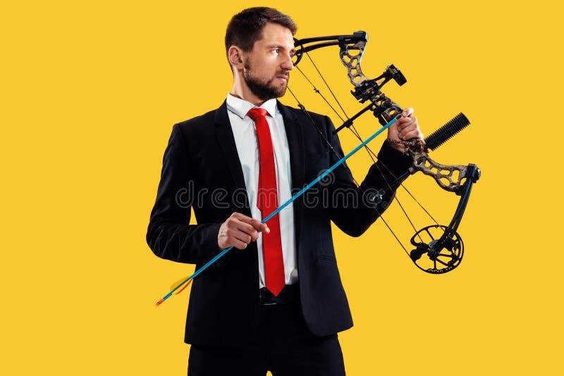 Geschäftsmann, der Ziel mit dem Pfeil und Bogen, lokalisiert auf gelbem Hintergrund anstrebt stockfoto