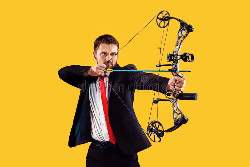 Geschäftsmann, der Ziel mit dem Pfeil und Bogen, lokalisiert auf gelbem Hintergrund anstrebt lizenzfreies stockbild