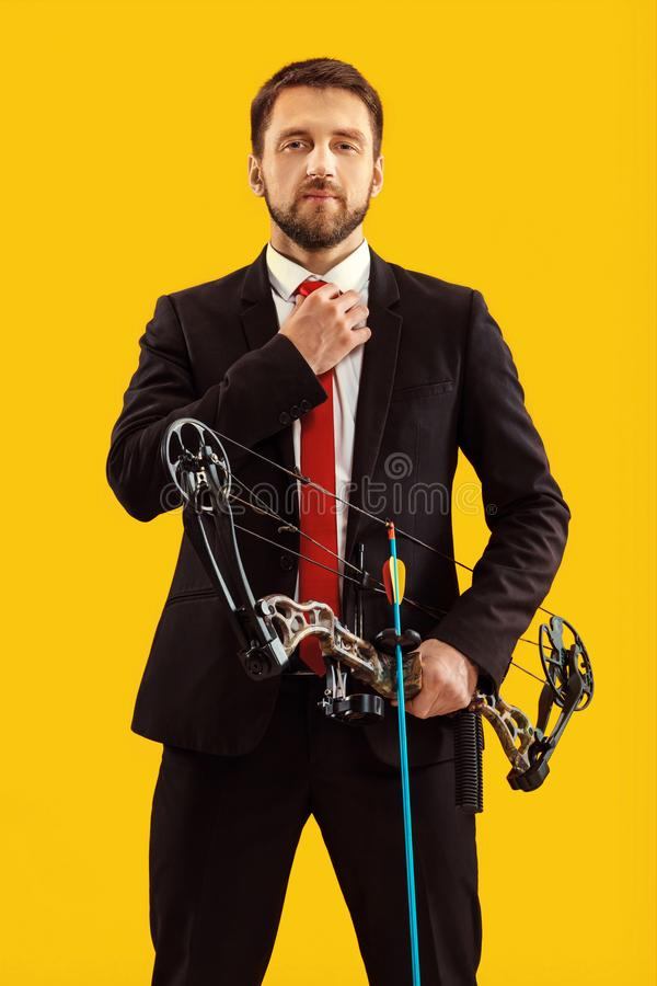 Geschäftsmann, der Ziel mit dem Pfeil und Bogen, lokalisiert auf gelbem Hintergrund anstrebt lizenzfreie stockbilder
