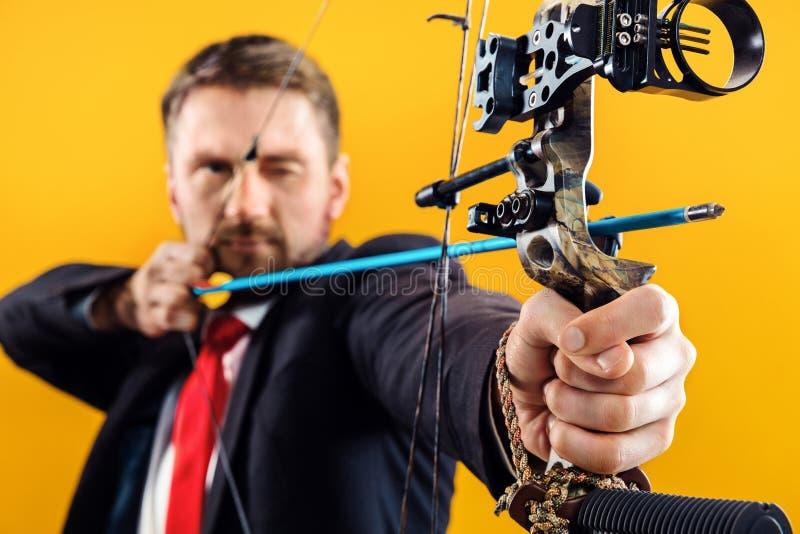 Geschäftsmann, der Ziel mit dem Pfeil und Bogen, lokalisiert auf gelbem Hintergrund anstrebt lizenzfreie stockfotografie