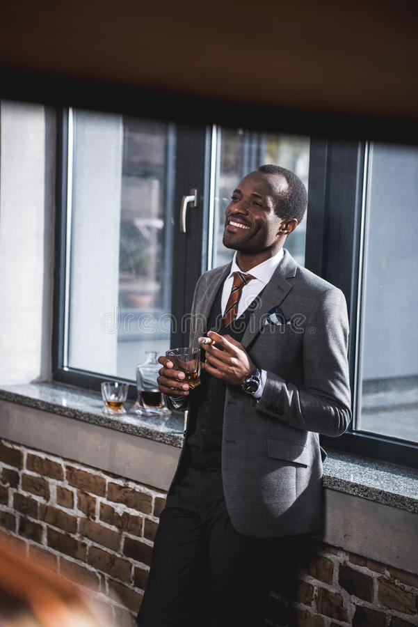 Geschäftsmann, der Zigarre und Glas Alkohol in den Händen hält stockbilder