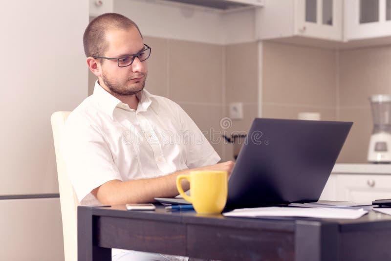 Gesch?ftsmann, der zu Hause an B?ro des Laptops arbeitet stockbilder