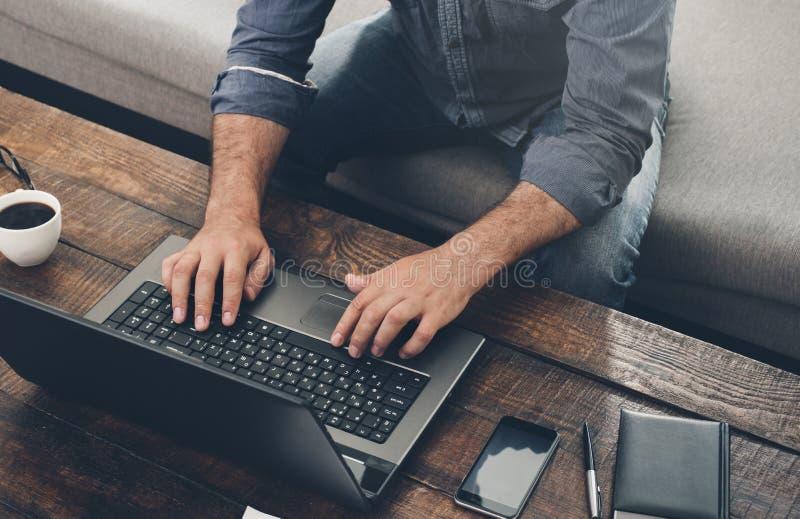Geschäftsmann, der zu Hause mit Laptop auf dem Sofa arbeitet lizenzfreies stockbild