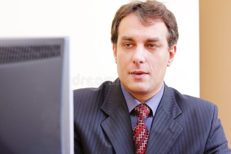 Geschäftsmann, der zum Überwachungsgerät schaut lizenzfreie stockfotos