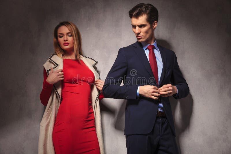 Geschäftsmann, der zurück seine Klage und Blicke an seiner Freundin knöpft lizenzfreies stockbild