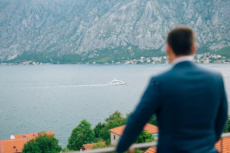 Geschäftsmann, der zur Yacht schaut Bucht von Kotor, die Stadt von Prca lizenzfreie stockfotografie