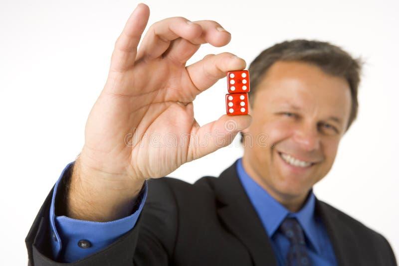 Geschäftsmann, der zwei rote Würfel anhält lizenzfreies stockfoto