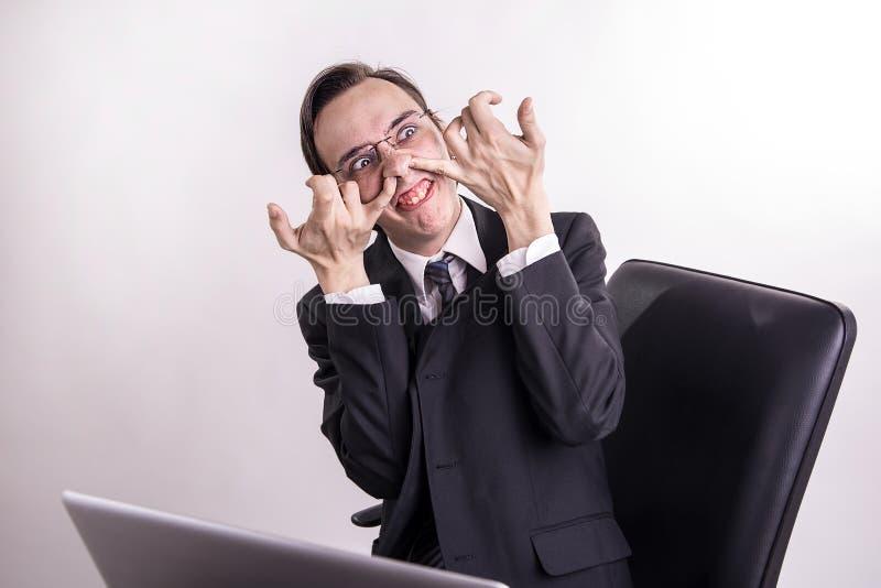 Geschäftsmann des zweifelhaften Geschäfts, der im Büro scherzt, Gesicht verzieht und grinst stockfoto