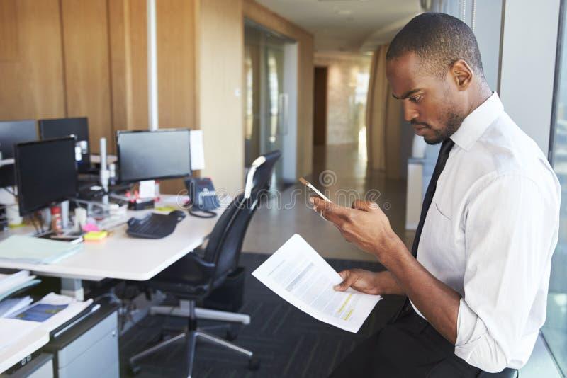 Geschäftsmann-At Desk Checking-Mitteilungen am Handy lizenzfreie stockfotos