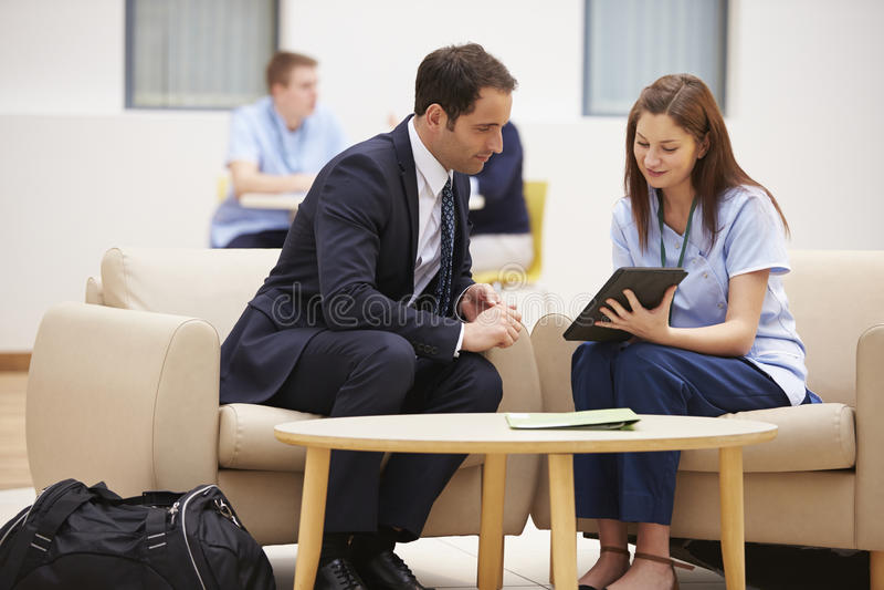 Geschäftsmann-Discussing Results With-Krankenschwester On Digital Tablet stockfotografie