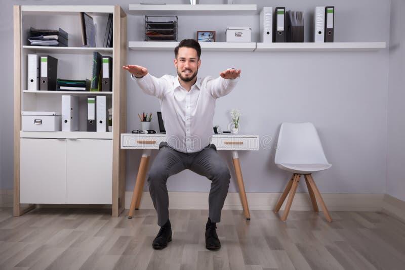 Geschäftsmann-Doing Workout In-Büro stockfoto