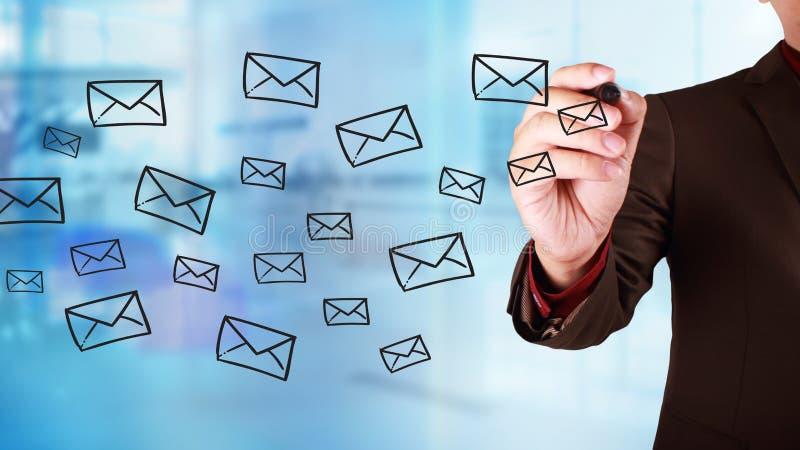 Geschäftsmann Draw auf virtuellem Schirm mit den E-Mail-Ikonen, die vorbei fliegen stockfoto
