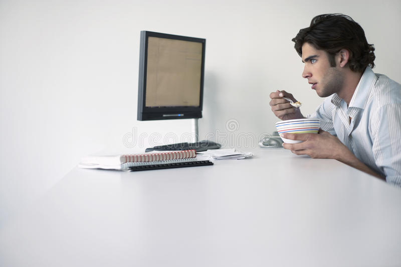 Geschäftsmann-Eating At Office-Schreibtisch lizenzfreies stockfoto