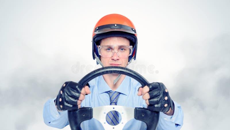 Geschäftsmann in einem roten Sturzhelm mit Lenkrad lizenzfreie stockfotos