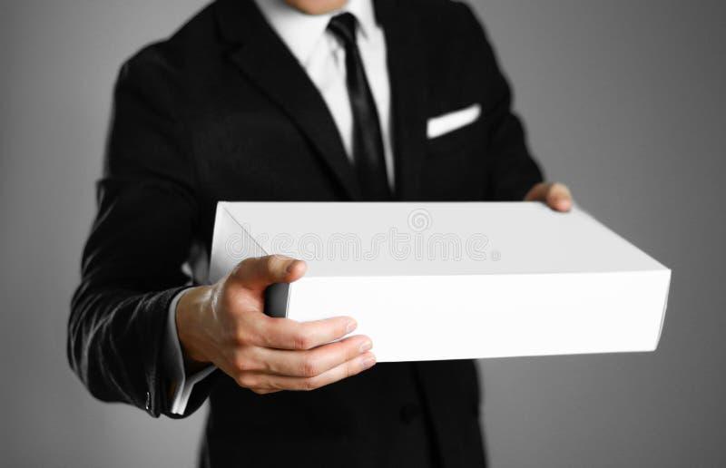 Geschäftsmann in einem schwarzen Anzug, der einen weißen Kasten hält Abschluss oben Lokalisierter Hintergrund lizenzfreies stockfoto