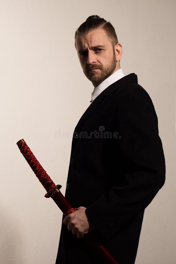 Geschäftsmann in einem schwarzen Anzug mit einer Samuraiklinge lizenzfreies stockbild