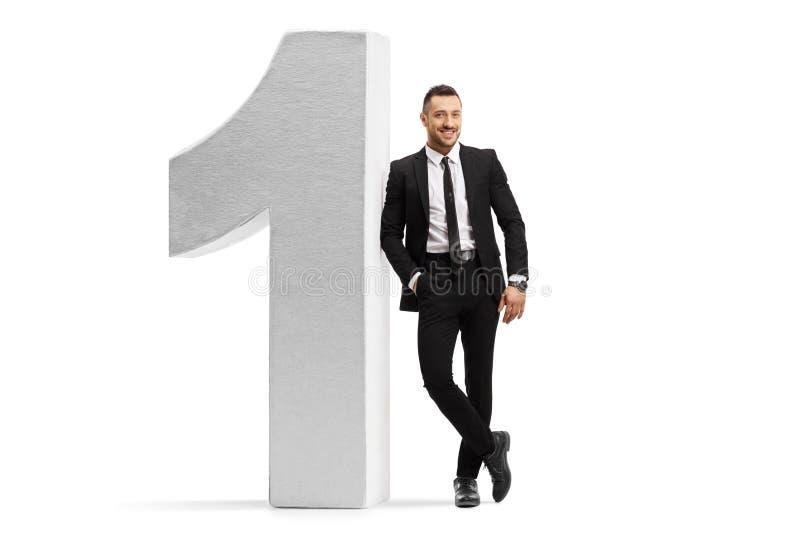 Geschäftsmann in einem schwarzen Anzug und in einer Bindung, die auf Nummer Eins sich lehnen lizenzfreie stockbilder