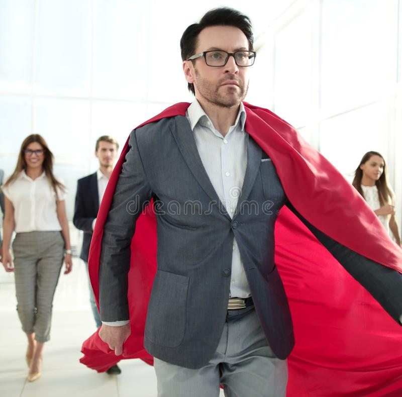 Geschäftsmann in einem Superheld ` s Mantel ist vor dem Geschäftsteam stockbild