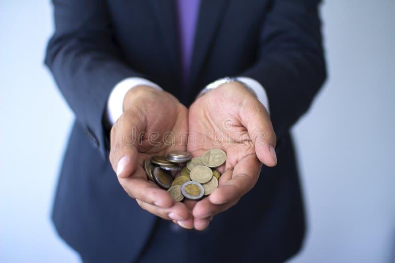 Geschäftsmann in einer Klage, die peruanische Münzen, Nuevos-Sohlenwährungskonzept hält stockbilder