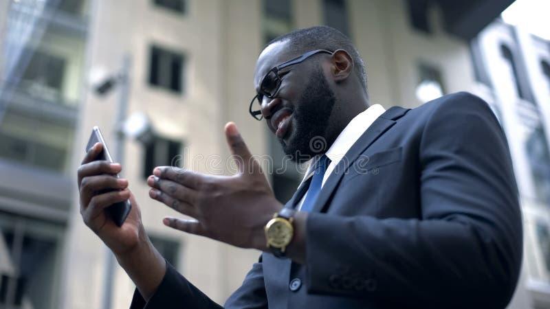Geschäftsmann erhält Umkippen nach gelesenen schlechten Nachrichten auf dem Smartphone, abgefeuert, Problem bei der Arbeit stockfotos