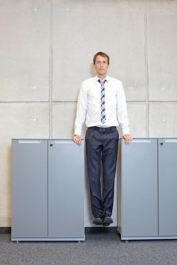 Geschäftsmann in formellen Kleidungsstücken, zwischen Büroschränken suspendiert lizenzfreie stockbilder