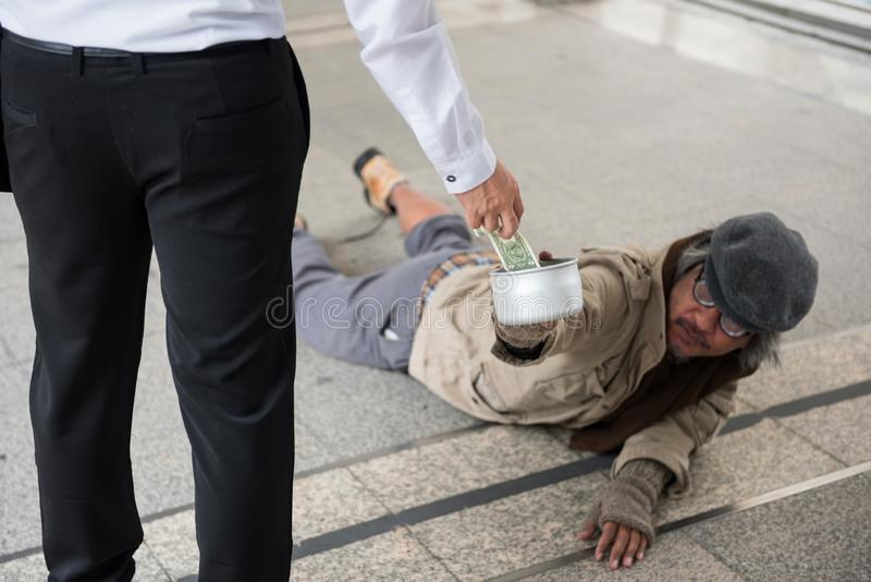 Geschäftsmann geben behindertem obdachlosem Mann Geld lizenzfreie stockbilder