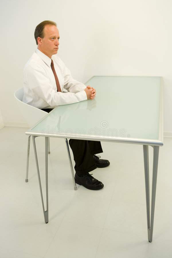 Geschäftsmann gesessen am leeren Schreibtisch lizenzfreie stockfotografie