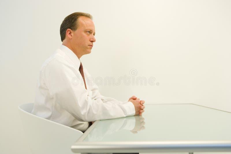 Geschäftsmann gesessen am Tisch stockbild