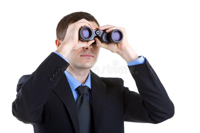 Geschäftsmann getrennt auf dem weißen Schauen durch Ferngläser lizenzfreies stockfoto