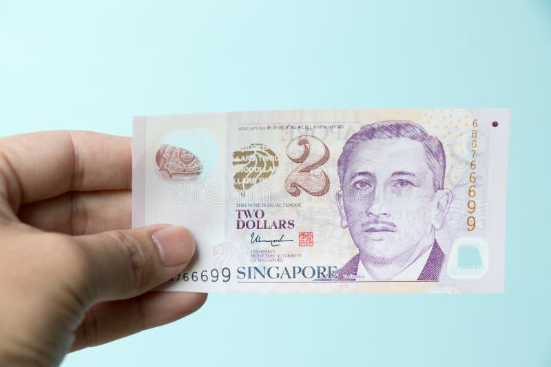 Geschäftsmann-Griff 2 Singapur-Dollarbanknote auf blauem konkretem Hintergrund lizenzfreie stockfotografie
