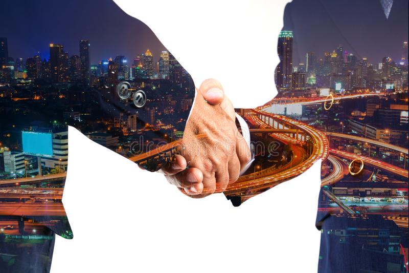 Geschäftsmann Grußshakehand-Abkommen mit der modernen Stadt, die nachts glänzt lizenzfreies stockbild