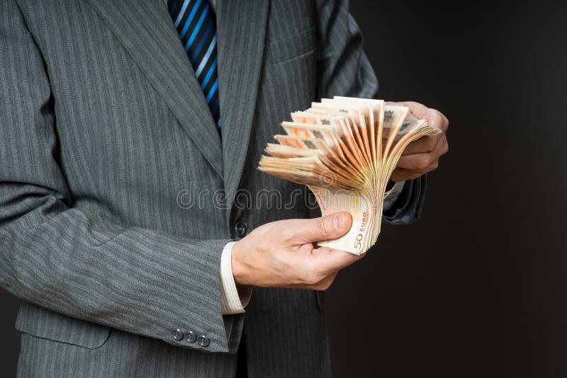 Geschäftsmann hält Bargeld, Fan von fünfzig Euros Person zählt Geld Geschäftsmannhände und Eurorechnungen lizenzfreies stockbild